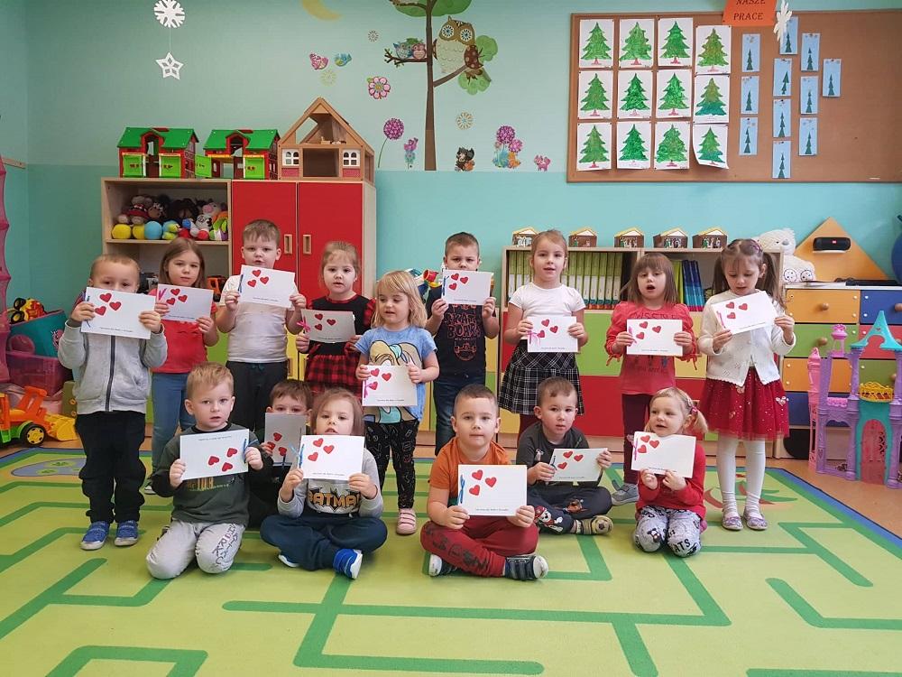 Grupa przedszkolaków trzymająca w dłoniach obrazki z sercami. Część dzieci siedzi na zielonym dywanie, a część stoi za nimi.