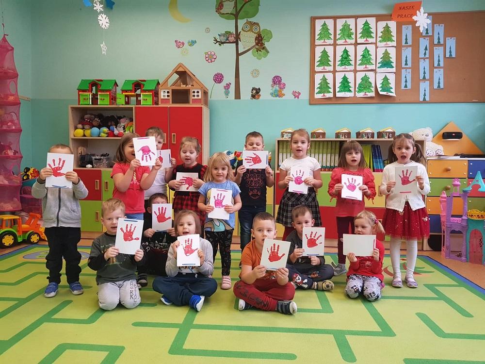 Grupa przedszkolaków trzymająca w dłoniach obrazki z odbitymi na kartonie swoimi dłoniami. Część dzieci siedzi na zielonym dywanie, a część stoi za nimi.