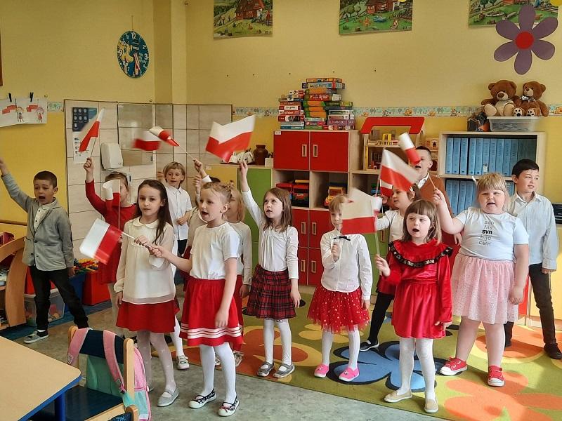 przedszkolaki w biało- czerwonych strojach z flagami w dłoniach.